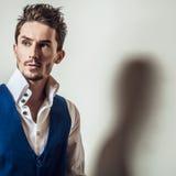 Elegant ung stilig man i den vita ståenden för skjorta- & väststudiomode Royaltyfria Foton