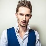 Elegant ung stilig man i den vita ståenden för skjorta- & väststudiomode Royaltyfri Foto