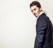Elegant ung stilig man i dräkt Manligt ta av ens kläder Royaltyfri Foto