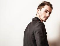 Elegant ung stilig man i svart dräkt Manligt ta av ens kläder Arkivfoto