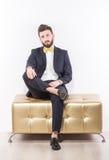 Elegant ung stilig man i svart klassisk dräkt med den gula flugan Arkivfoto