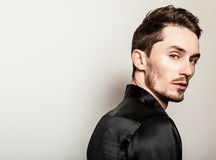 Elegant ung stilig man i svart siden- skjorta Manligt ta av ens kläder Royaltyfri Fotografi