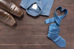 Elegant uppsättning: bruna skor för man` s, blå skjorta, blå slips, på Arkivbild