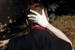 Elegant ursnygg brud som kramar den stilfulla brudgummen hand i vit glov arkivbild