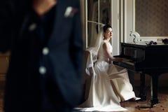 Elegant ursnygg brud som spelar fortepianoen i rikt gammalt rum a royaltyfri bild