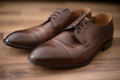 Elegant, used brown leather male shoes set on a brown wooden table. Fashionable, polished Oxford male shoes in pair, selective focus, on brown background Royalty Free Stock Photography