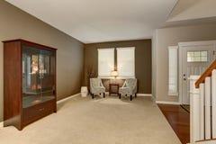 Elegant vardagsrum i brunt tonar med två klassiska fåtöljer och fåfängakabinett royaltyfri fotografi
