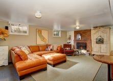 Elegant vardagsrum med lädersoffauppsättningen, tegelstenspisen och det antika träkabinettet Royaltyfri Fotografi