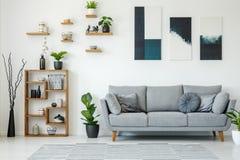 Elegant vardagsruminre med en grå soffa, trähyllor, p royaltyfri bild
