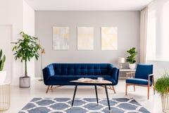 Elegant vardagsruminre med en uppsättning av mörker - blå soffa och fåtölj Moderna målningar för guld och för silver på bakgrunde royaltyfri foto