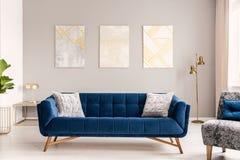 Elegant vardagsruminre med garneringar för en bekväm stor blå sammetsoffa och guld Verkligt foto royaltyfria bilder