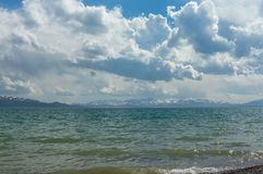 Elegant view of the mountain lake. Son Kul with curly clouds and blue sky Royalty Free Stock Images