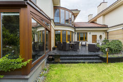 Elegant villa terrace with garden furniture. Elegant terrace with garden furniture in the backyard of villa with many windows Stock Photos