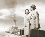 Elegant vintage couple leaving with luggage. Elegant vintage couple walking and holding suitcases with steam train on background, travel concept Stock Image