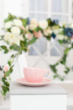 Elegant vintage cup on background of terrace overgrown with flowers Stock Photo