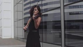 Elegant violinist in black dress near glass building. Urban art concept stock footage