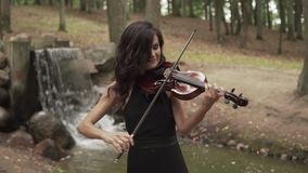 Elegant violinist plays with inspiration. Girl in dress playing violin in forest. Elegant violinist plays with inspiration. Beautiful girl in black dress playing stock footage