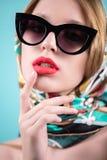 Elegant elegant vrouwelijk model in manierzonnebril wat betreft hand het gezicht op blauwe achtergrond Sluit omhoog royalty-vrije stock afbeelding