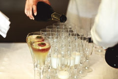 Elegant waiter pouring champagne in glasses at wedding ceremony Royalty Free Stock Photo