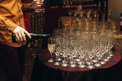 Elegant waiter pouring sparkly champagne into group of glasses a. T luxury business corporate retreat party, restaurant catering concept royalty free stock images