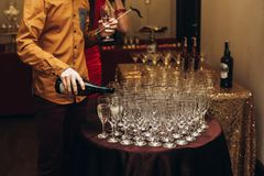 Elegant waiter pouring sparkly champagne into group of glasses a. T luxury business corporate retreat party, restaurant catering concept stock photography