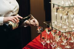 Elegant waiter pouring sparkly champagne into group of glasses a. T luxury business corporate retreat party, restaurant catering concept stock photo