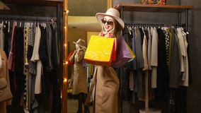 Elegant Lady with Bags. Elegant, wealthy lady buying clothes in cozy, expensive shop, spending free time doing her favourite thing on typical weekend afternoon stock video footage