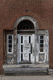Elegant, weathered white door with ornate details on rustic brick wall Stock Photos
