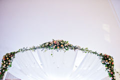 Elegant wedding arch of table newlyweds with many flowers. Royalty Free Stock Photos