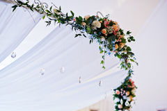 Elegant wedding arch of table newlyweds with many flowers. Stock Photos