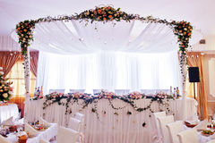 Elegant wedding arch of table newlyweds with many flowers. Stock Photography