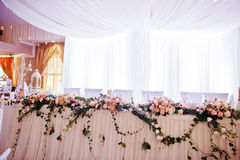 Elegant wedding arch of table newlyweds with many flowers. Stock Photo