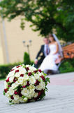 Elegant wedding bouquet with many roses on blur newlywed backgro. Unds Royalty Free Stock Photography