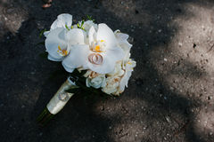 Elegant wedding bouquet of white orchids with golden wedding rin. Gs on asphalt Royalty Free Stock Photography