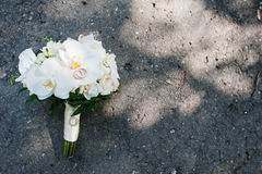 Elegant wedding bouquet of white orchids with golden wedding rin. Gs on asphalt Stock Image