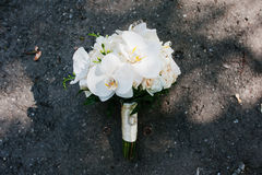 Elegant wedding bouquet of white orchids with golden wedding rin Stock Photos