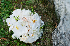 Elegant wedding bouquet of white orchids with golden wedding rin. Gs on grass background stone Stock Photo