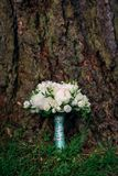 Wedding bouquet of white and pink peonies and roses lying on a meadow Stock Photos