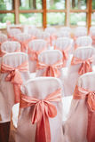 Elegant Wedding Ceremony. An elegant wedding ceremony seating setup with white chair covers and coral pink bows decor Stock Image