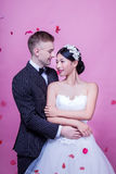 Elegant wedding couple embracing while standing against pink background Royalty Free Stock Image