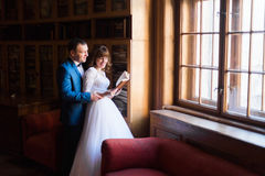 Elegant wedding couple at old library. Bride and groom standing witn book near window Stock Photography