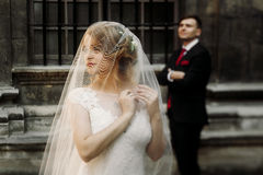 Elegant wedding couple posing in old courtyard in european stree. T. luxury bride under veil and groom standing. romantic sensual moment Stock Image