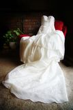 Elegant Wedding Dress on Chair. Traditional white wedding dress with a long train displayed on a red chair in living room Royalty Free Stock Photography