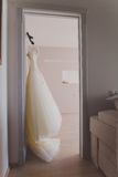 Elegant wedding dress hanging on a door awaiting Royalty Free Stock Photo