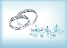 Elegant wedding rings with brilliants. Elegant jewelry  rings  with brilliants and flowers on blue card for invitation on wedding day Royalty Free Stock Photos