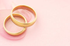 Elegant wedding rings with petals. On pink background with copy space Royalty Free Stock Image