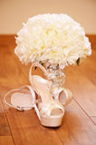 Elegant wedding shoes. With beautiful bouquet on the floor Royalty Free Stock Photos