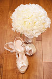 Elegant wedding shoes. With beautiful bouquet on the floor Stock Photography