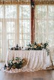 Elegant wedding table in the style of vintage and rustic decorated with flowers, white lace, tablecloth and candles. Vertical royalty free stock photography