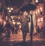 Elegant well-dressed couple outdoors. Elegant couple with umbrella outdoors on rainy evening Royalty Free Stock Photography